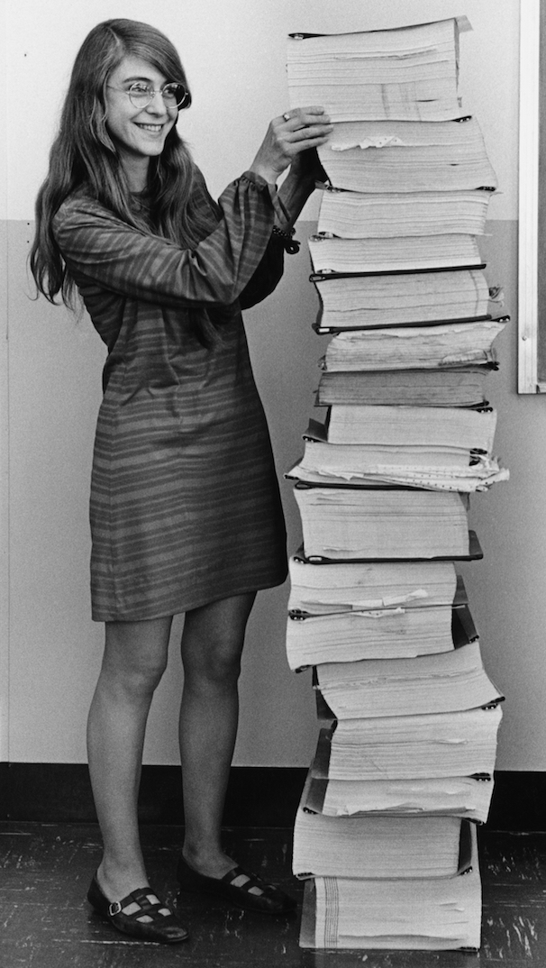 Margaret Hamilton standing with a stack of paper.